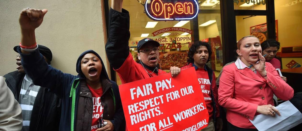 Direitos. Trabalhadores de redes de fast food protestam pelo aumento do salário mínimo, em Nova York Foto: Emmanuel Dunand/AFP