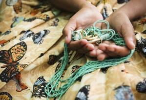 Adolescente carioca, vítima de preconceito religioso, segura sua guia (delogum) e veste a saia baiana, símbolos do candomblé Foto: Laura Marques / Agência O Globo