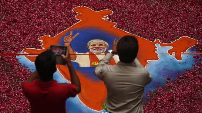 Eleitores fotografam imagem de Narendra Modi feita com pó colorido e rosas Foto: Saurabh Das / AP