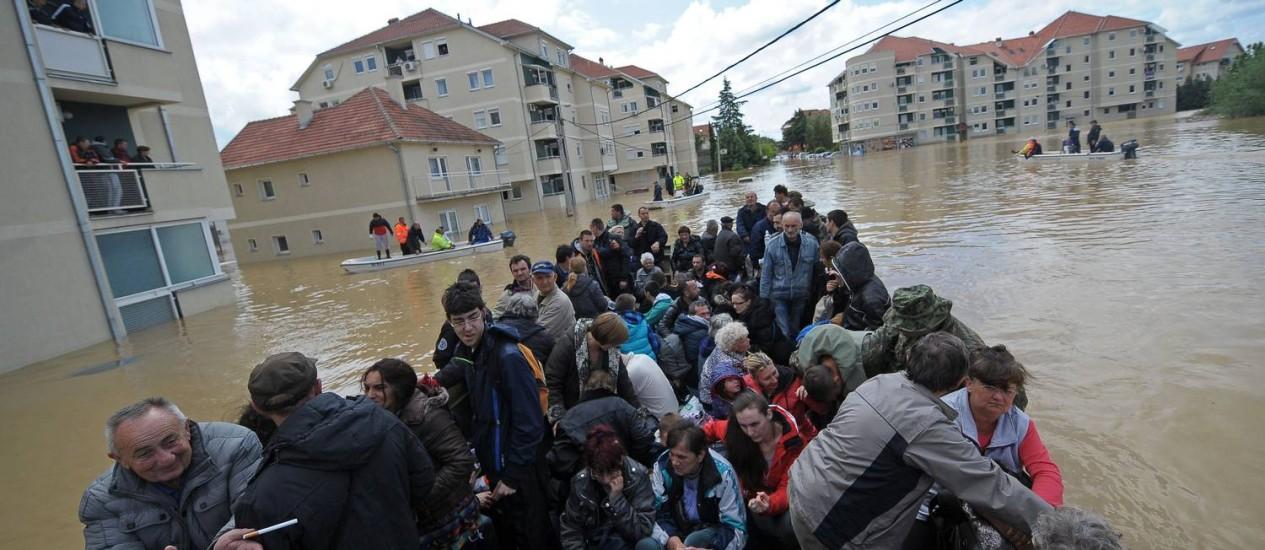 Grande grupo é evacuado em um veículo anfíbio por ruas alagadas na cidade sérvia de Obrenovac Foto: ALEXA STANKOVIC / AFP