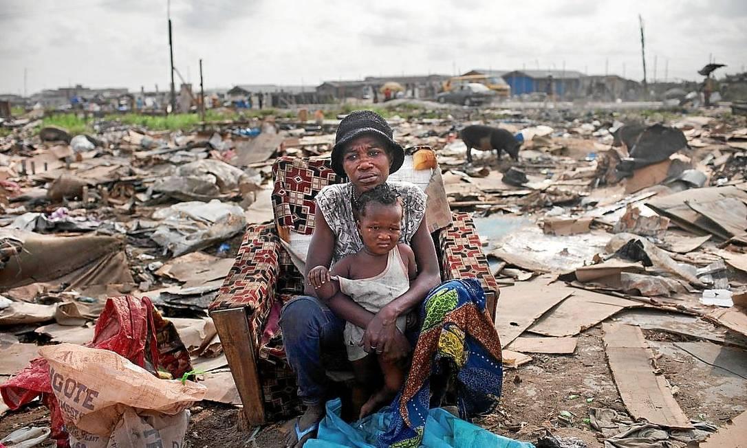 """<cutline_leadin>Pobreza extrema.</cutline_leadin> Mãe e filho em meio em favela em Lagos Foto: Samule James/""""The New York Times""""/26-2-2013"""