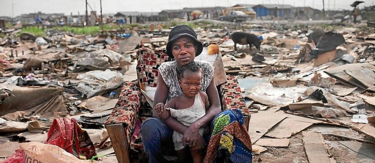 """Pobreza extrema. Mãe e filho em meio em favela em Lagos: 60% da população vivem com menos de US$ 1 por dia Foto: SAMUEL JAMES / Samule James/""""The New York Times""""/26-2-2013"""
