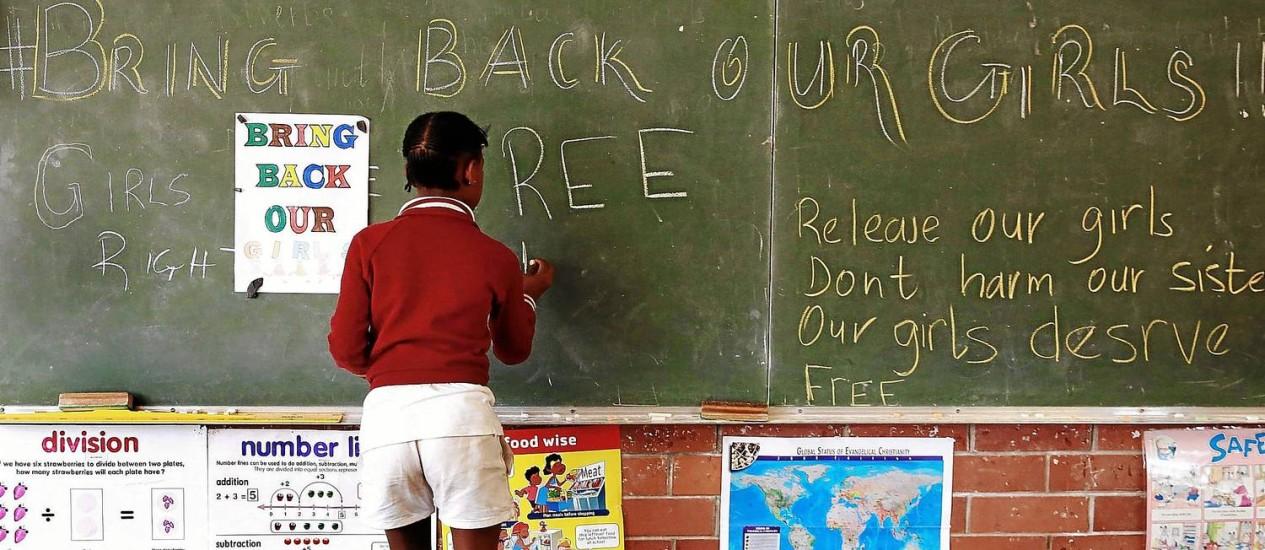 'Tragam de volta nossas meninas'. Aluna de uma escola em Durban, na África do Sul, escreve no quadro-negro a mensagem que roda o mundo, pedindo o retorno das jovens estudantes nigerianas sequestradas pelo Boko Haram Foto: AFP/15-04-2014