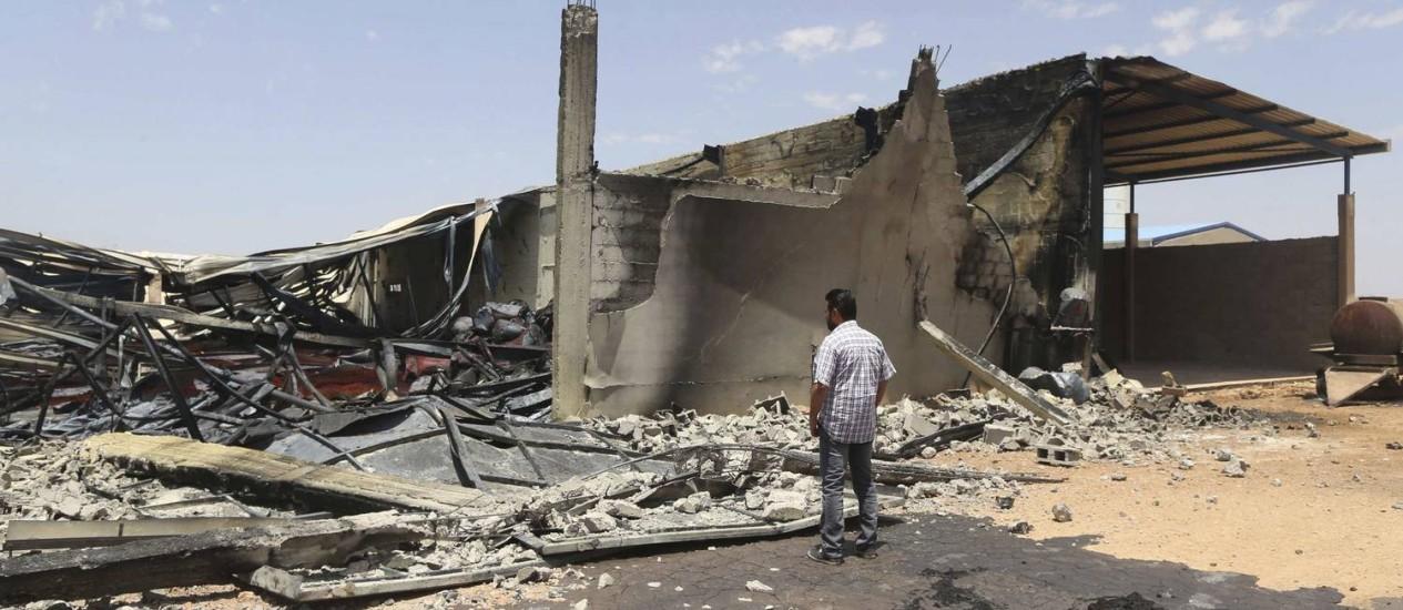 Homem observa depósito destruído após confrontos entre milícias islâmicas e forças líbias, em Benghazi Foto: ESAM OMRAN AL-FETORI / REUTERS