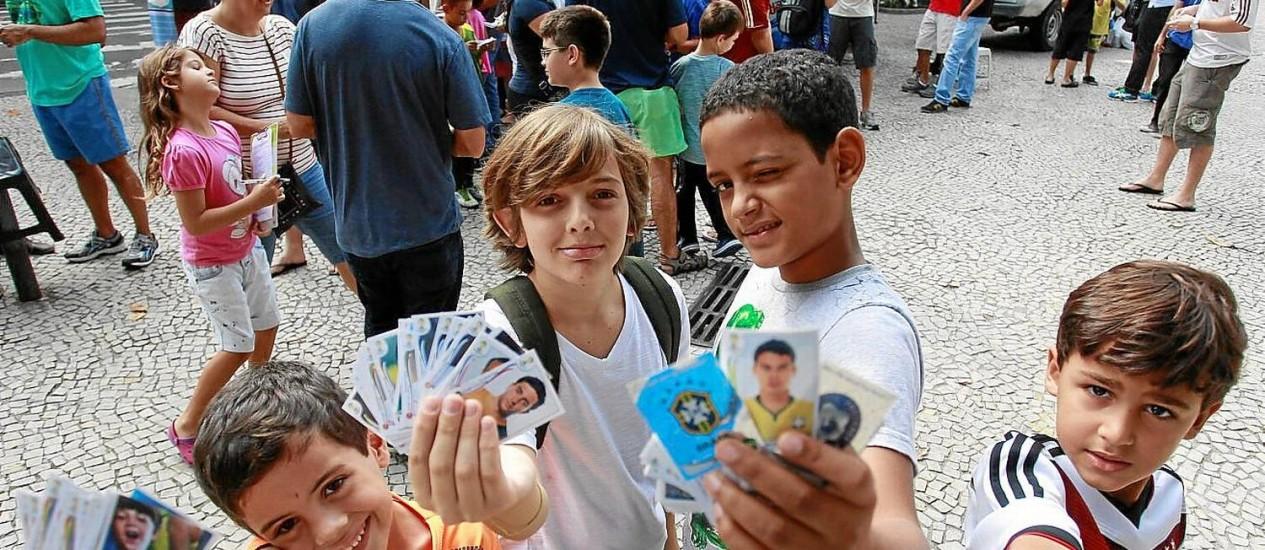 Reta final. Meninos ansiosos em obter as últimas figurinhas de seus álbuns ainda antes do início da Copa Foto: Márcio Alves / Agência O Globo