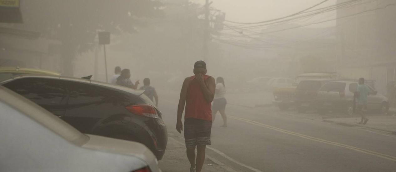 Homem protege o rosto da poeira após implosão de antiga fábrica no bairro de Irajá Foto: Guilherme leporace / Agência O Globo
