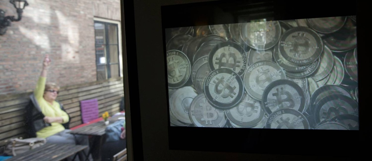 Tela de caixa eletrônico exibe imagem das moedas virtuais em um bar em Amsterdam Foto: Peter Dejong / AP