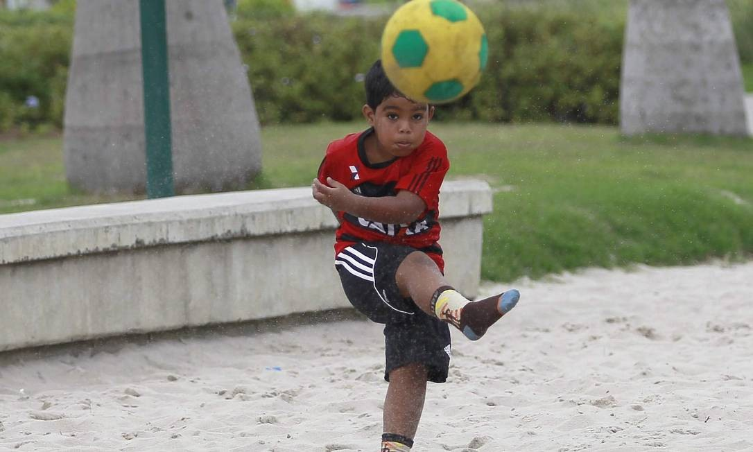Menino joga futebol na areia Foto: Márcio Alves / Agência O Globo