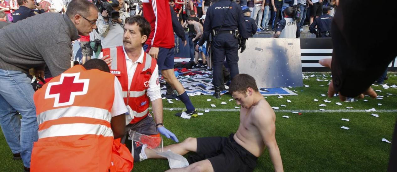 Um torcedor do Osasuna é atendido no campo após a queda da grade do estádio Foto: AP