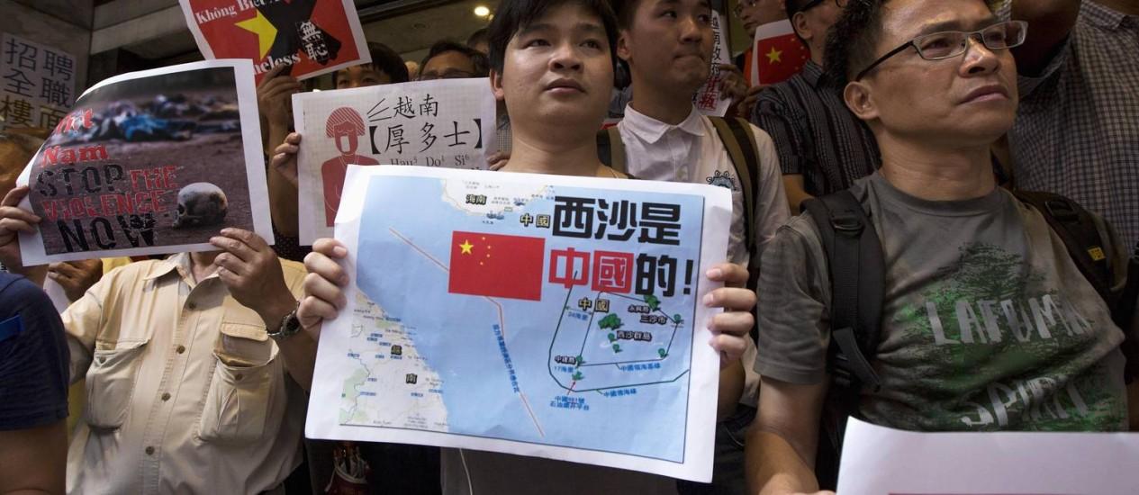 Em Hong Kong, manifestantes anti-Vietnã seguram cartazes com palavras de ordem e uma foto mostrando um mapa do Mar da China do Sul, incluindo as Ilhas Paracel, durante um protesto em defesa do território da China Foto: TYRONE SIU / REUTERS