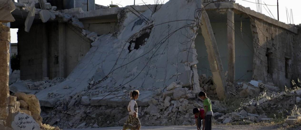 Crianças brincam perto de prédio destruído na cidade síria de Idlib, no Noroeste do país Foto: KHALIL ASHAWI / Reuters