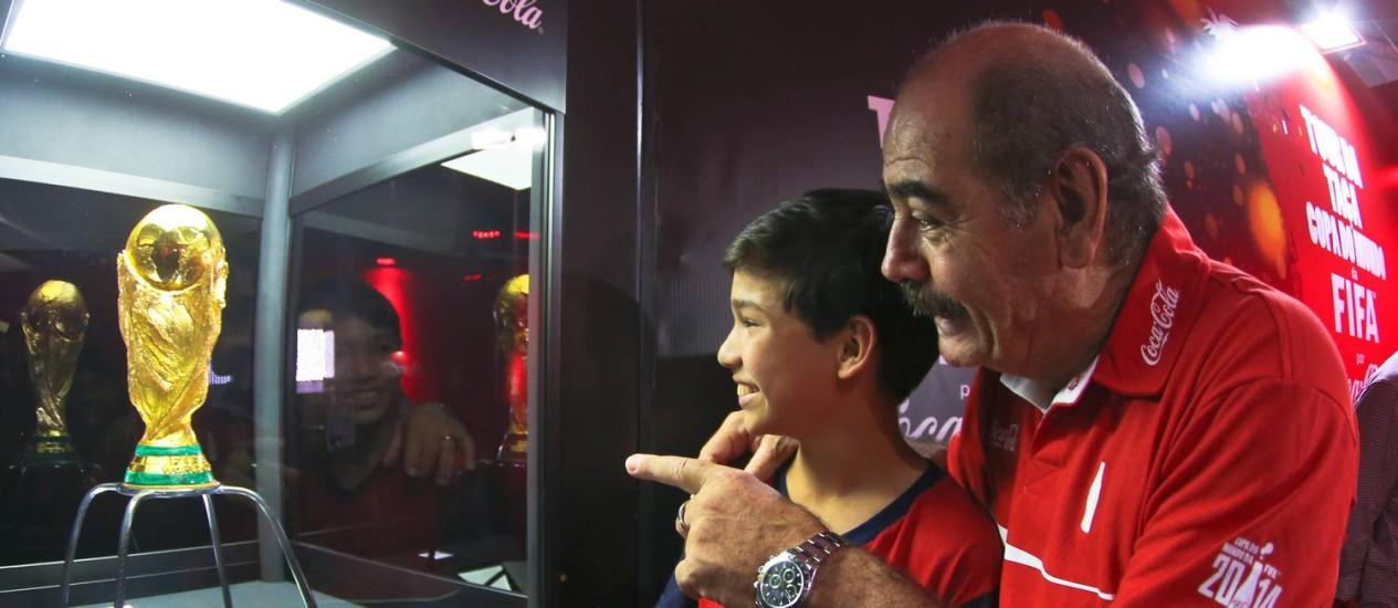 Ricardo Albuquerque dos Santos, de 14 anos, ao lado de Rivellino, se emociona ao ver de perto a taça Foto: Divulgação / Inovafoto/Coca Cola Brasil