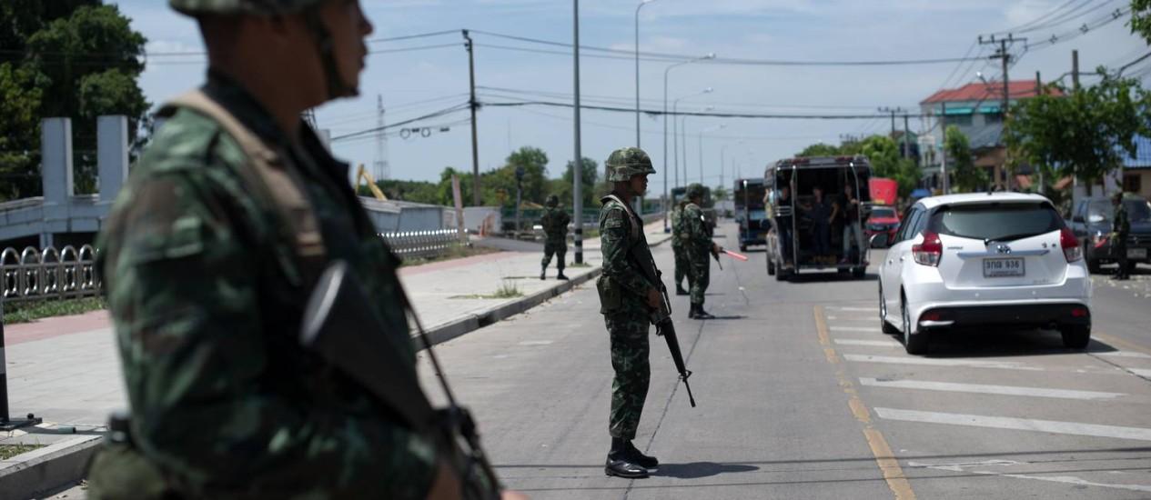 Soldados do Exército tailandês se posicionam diante de um posto de controle perto de onde manifestantes pró-governo se concentram por dias nos arredores de Bangcoc Foto: NICOLAS ASFOURI / AFP