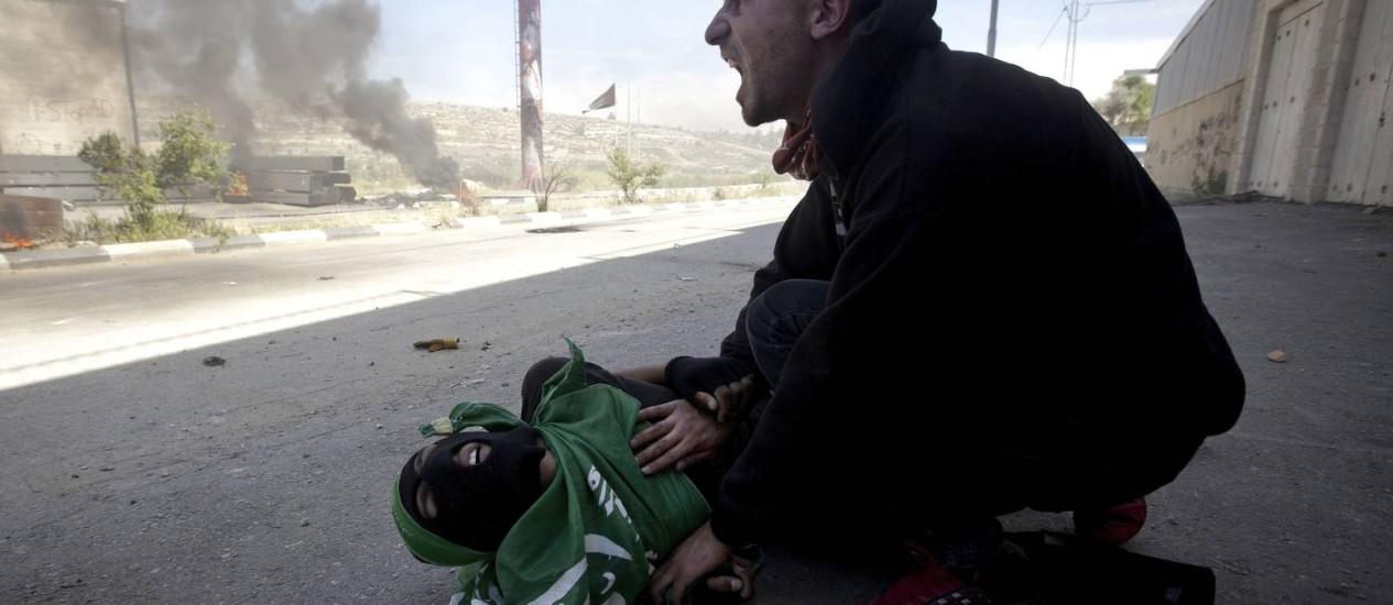 Um palestino grita diante do corpo do adolescente Mohammad Abu Daher, em Ramallah. ONG afirma que jovens não representavam ameaça Foto: Majdi Mohammed / AP/15-5-2014