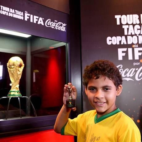 Augusto Nogueira, de 10 anos, posa com a taça da Copa do Mundo ao fundo Foto: Wander Roberto/Inovafoto