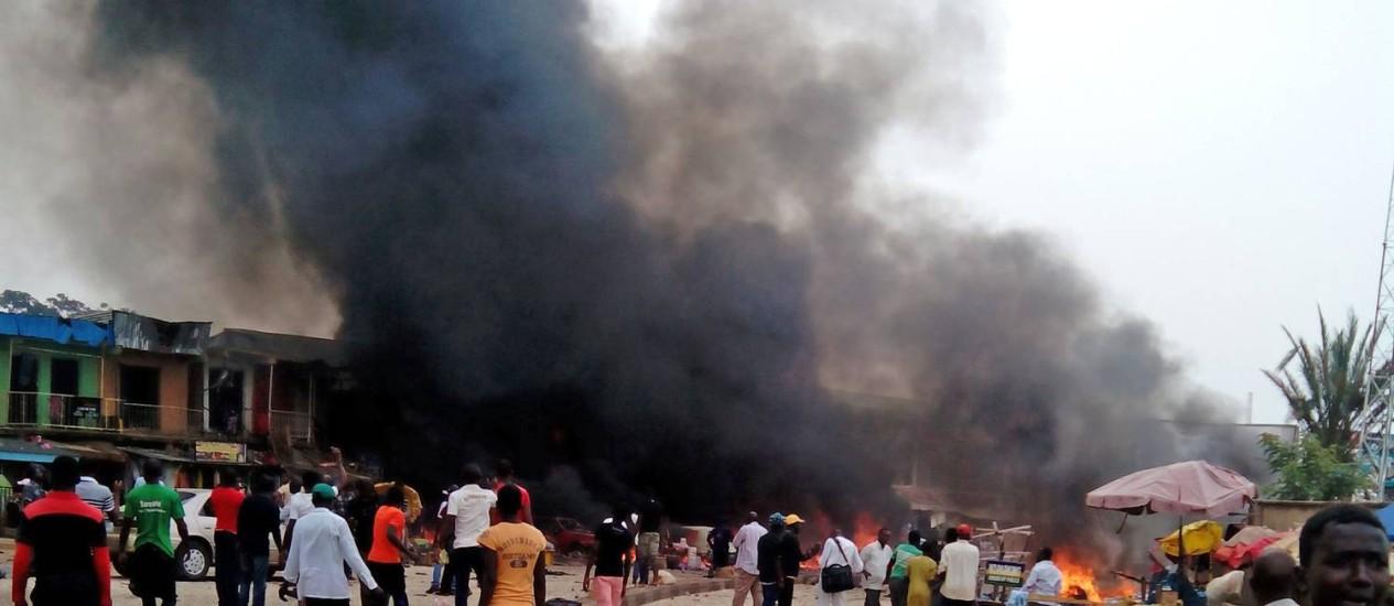 Uma coluna de fumaça se ergue do mercado e do ponto de ônibus atingidos por uma explosão em Jos, na Nigéria, nesta terça-feira Foto: AP