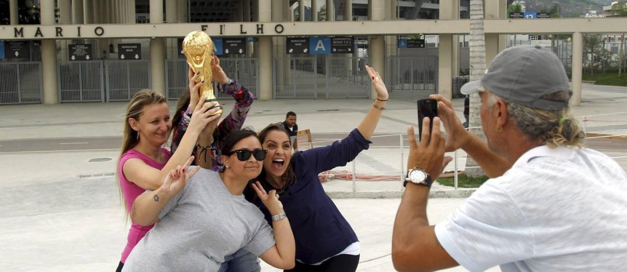Turistas posam com réplica da taça em gesso Foto: Gabriel de Paiva / Agência O Globo