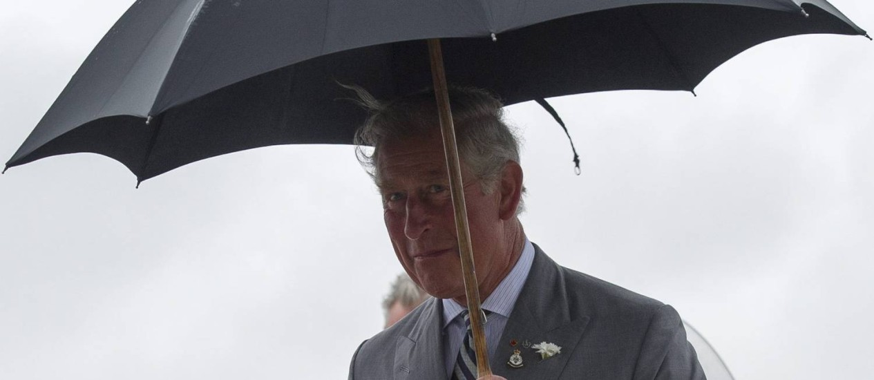 Príncipe Charles chega na chuva no aeroporto da base das forças canadenses em Winnipeg Foto: David Lipnowski / AP