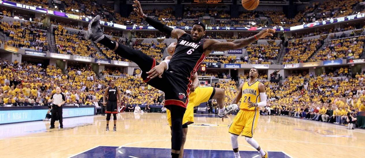 Brilhante. Mesmo marcado por David West do Indiana (21), LeBron James (6), do Miami Heat, conclui uma enterrada na vitória sobre o rival, em Indianápolis Foto: ANDY LYONS/AFP
