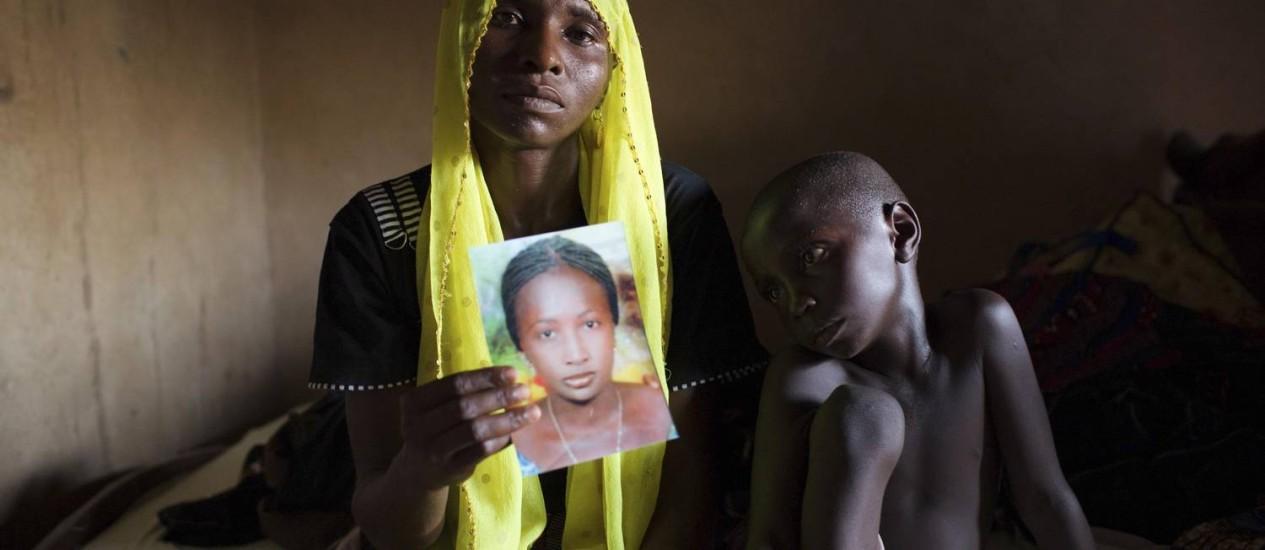 Nigéria. Sentada ao lado de sua filho Bukar, Rachel Daniel, de 35 anos, segura uma fotografia de sua filha, Rose, de 17 anos, sequestrada por militantes do grupo islamista Boko Haram Foto: JOE PENNEY / REUTERS