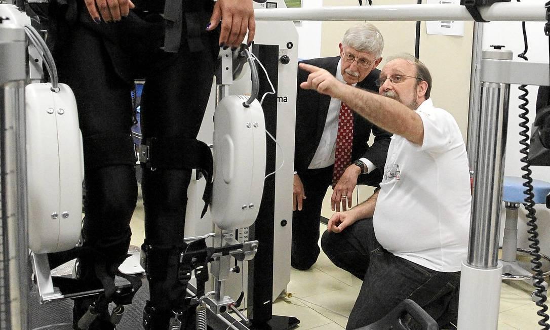 Nicolelis (de branco) mostra para Collins o exoesqueleto que fará com que um jovem paraplégico dê primeiro chute da Copa do Mundo Foto: / Fernando Donasci