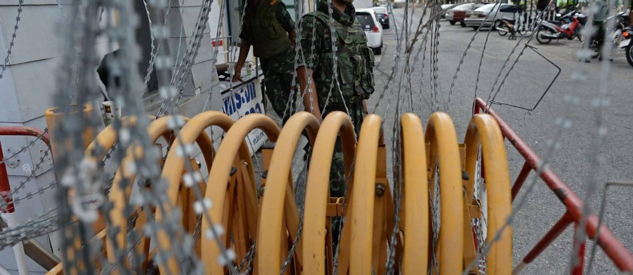 Um bloqueio é montado nas imediações do prédio do Ministério da Defesa, em Bangcoc. O anúncio do golpe foi feito pela TV Foto: CHRISTOPHE ARCHAMBAULT / AFP