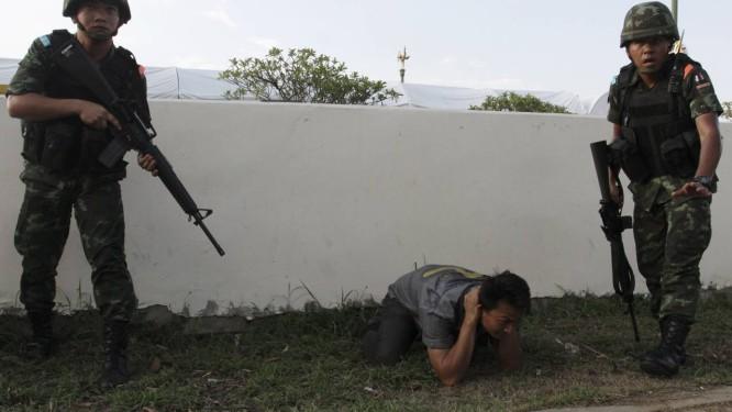 Soldados interpelam um homem ao desarmar o acampamento de manifestantes em Bangcoc Foto: STRINGER/THAILAND / REUTERS