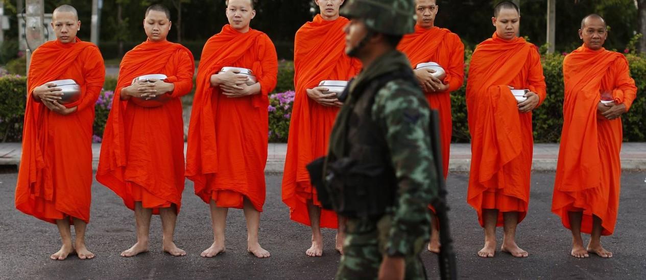Soldado caminha diante de monges budistas descalços que pedem dinheiro do lado de fora de um templo, perto da sede do governo em Bangcoc Foto: ATHIT PERAWONGMETHA / REUTERS