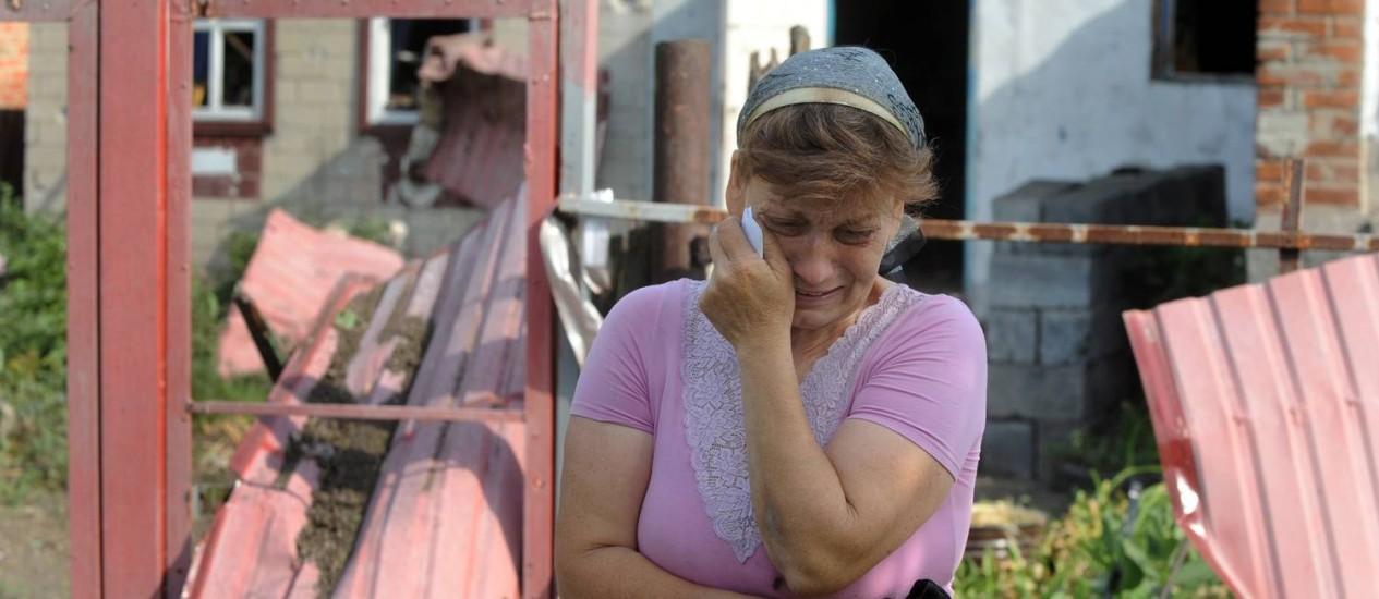 Mizan Mazasheva, de 50 anos, chora após sua casa ser destruída em combate entre forças ucranianas e tropas pró-Rússia Foto: VIKTOR DRACHEV / AFP
