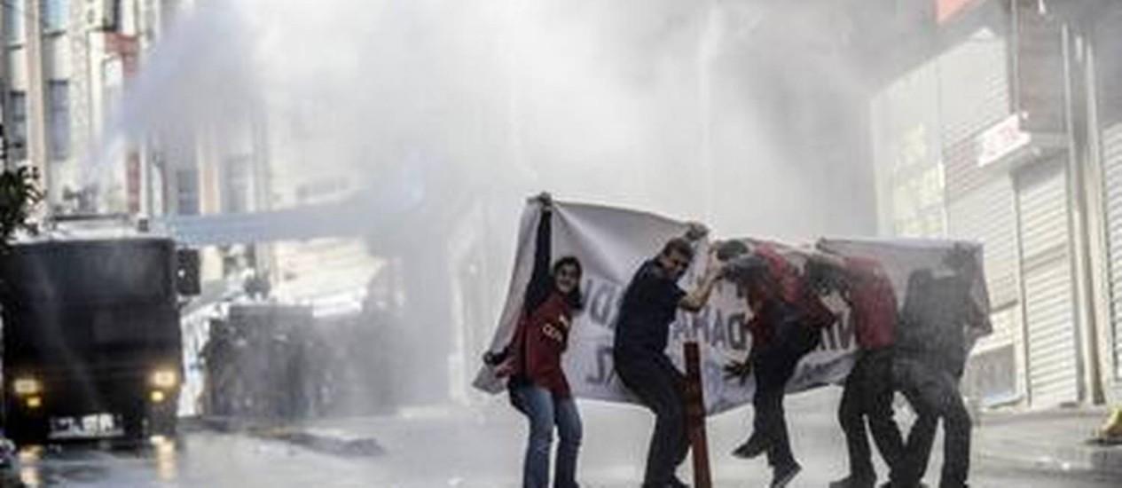 Manifestantes se protegem de canhões de água da polícia em protesto contra mortes em minas Foto: BULENT KILIC / AFP