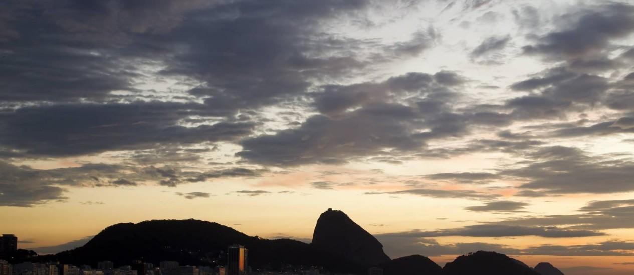 O céu parcialmente nublado no amanhecer desta sexta-feira. Na foto, o Pão de Açúcar visto da Praia de Copacabana Foto: Fernando Quevedo / Agência O Globo