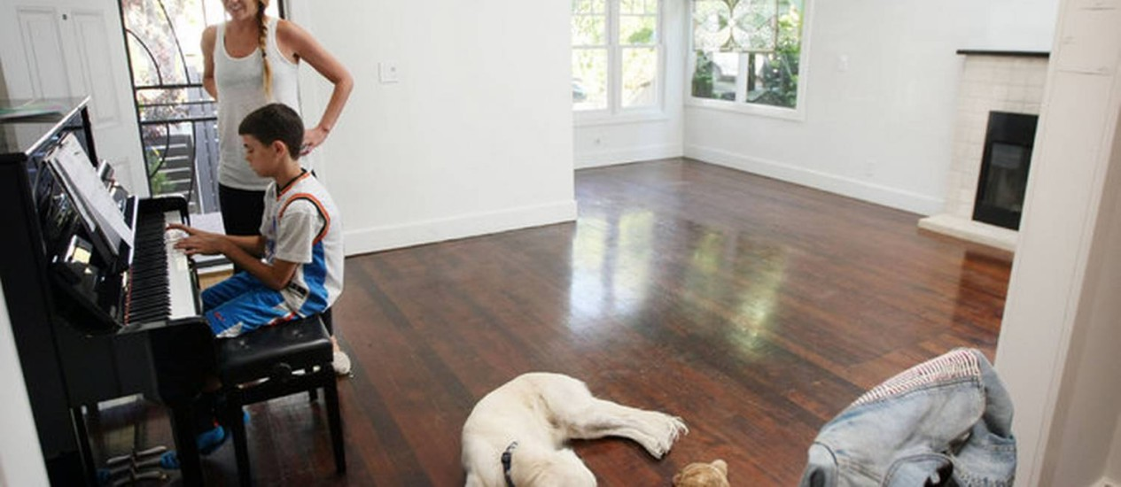 Jenna Dillon, e seu filho William, na casa que comprou há quatro anos. Agora, o imóvel valendo 67% a mais do que na época da aquisição Foto: NYT