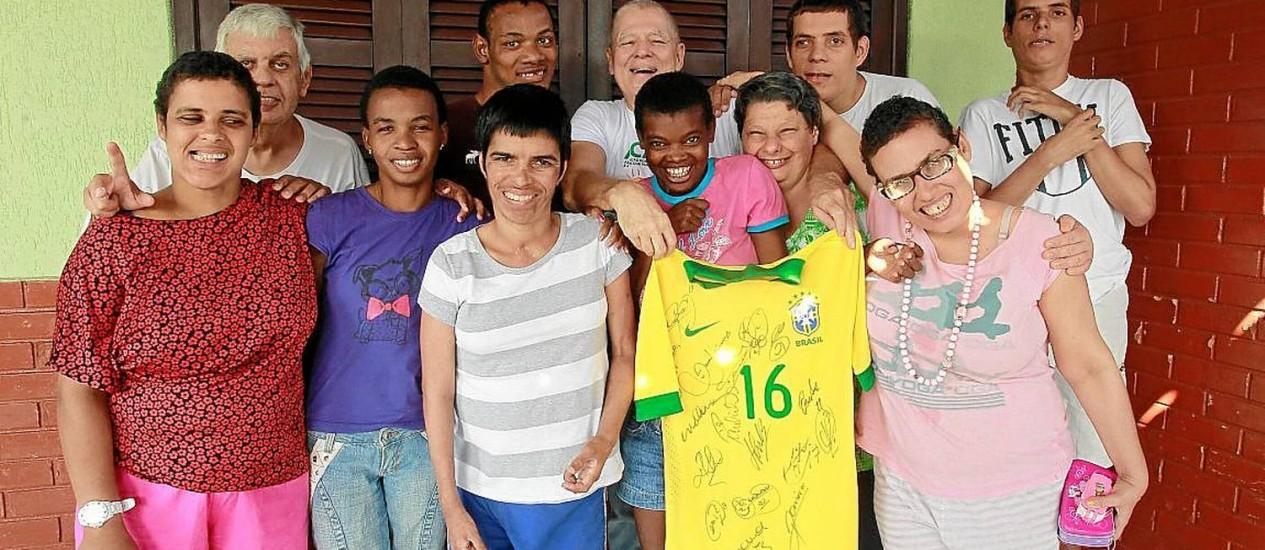 Clima de festa. Paulo Sá, um dos idealizadores da associação, exibe a camisa do Brasil junto a alguns dos abrigados Foto: Márcio Alves / Fotos de márcio alves