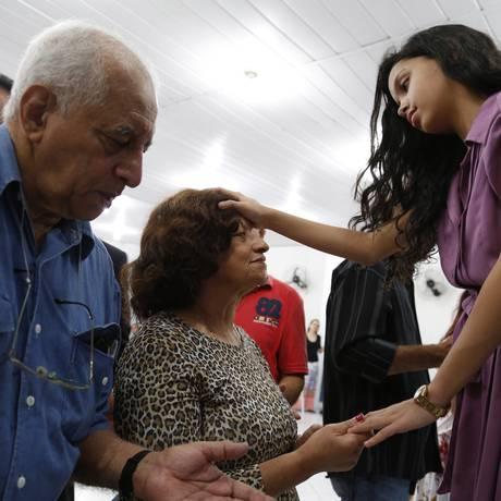 A missionária Alani Santos, de 10 anos, atende a fiéis na igreja onde seu pai é pastor. Foto: Simone Marinho / / Foto Simone Marinho