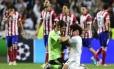 O goleiro Casillas e o lateral Marcelo se abraçam para festejar o título do Real Madrid na Liga dos Campeões, diante de jogadores desolados do Atlético de Madrid