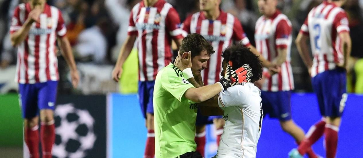 O goleiro Casillas e o lateral Marcelo se abraçam para festejar o título do Real Madrid na Liga dos Campeões, diante de jogadores desolados do Atlético de Madrid Foto: JAVIER SORIANO / AFP