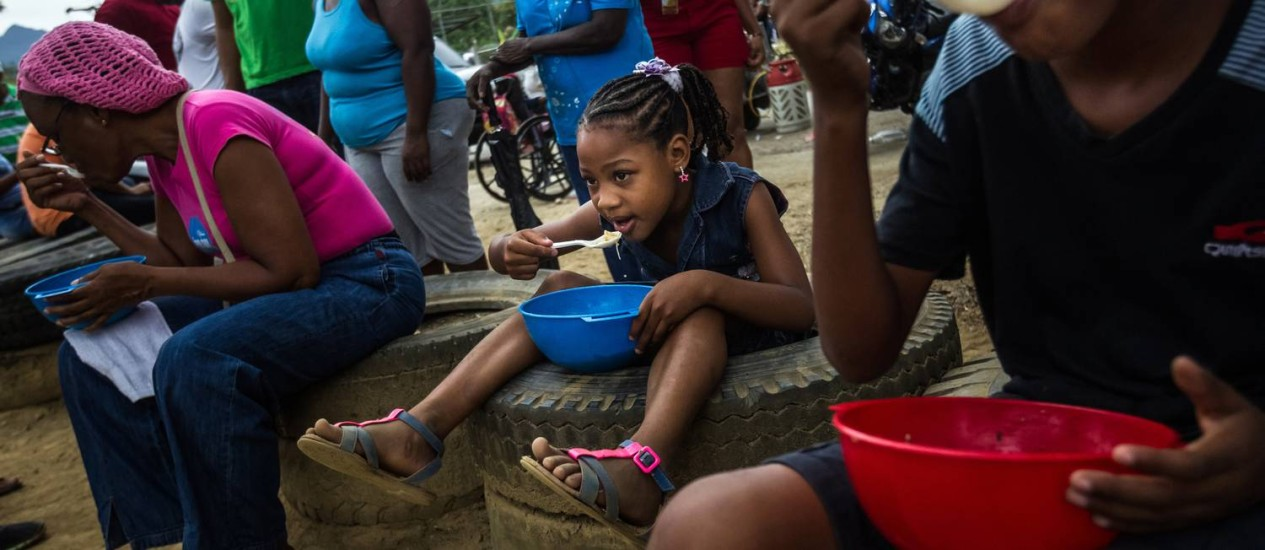 Moradores da região de Barlovento, na Venezuela, em uma distribuição gratuita de sopa Foto: Meridith Kohut / Bloomberg