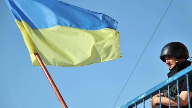 Tensão. Bandeira ucraniana tremula ao lado de soldado em posto de vigilância em Kharkiv, no conflituoso Leste do país: novo presidente não será re Foto: GENYA SAVILOV / AFP/16-5-2014