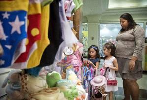 Catia Soares, com as duas filhas (Beatriz, de branco, e Isabela, de azul) precisou adequar os hábitos de consumo: criou o 'dia da carne' e o 'dia da fruta' Foto: Guito Moreto / O GLOBO
