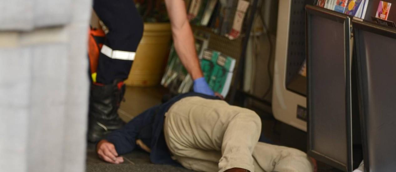 Membro da equipe de emergência examina os corpos de vítimas do ataque ao Museu Judaico de Bruxelas. Três pessoas morreram e uma ficou gravemente ferida no atentado neste sábado Foto: AFP