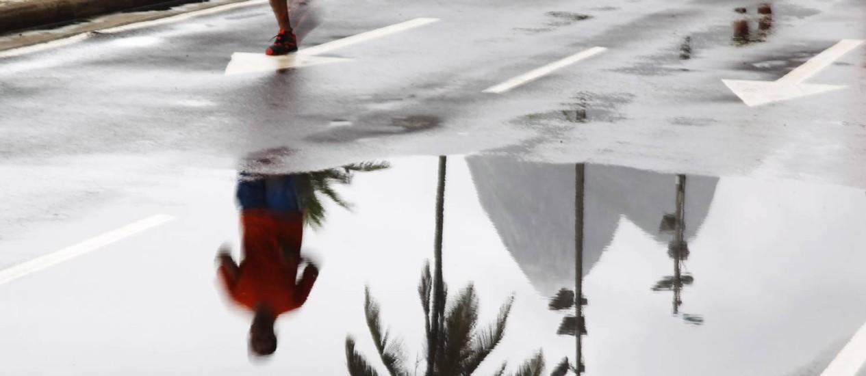 Refletido na poça d'água, homem aproveita o domingo para se exercitar Foto: Antonio Scorza / O Globo