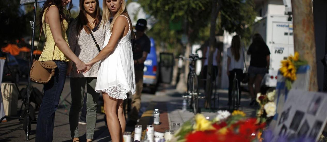 Jovens prestam homenagens aos estudantes assassinados por Elliot Rodger, na Califórnia Foto: LUCY NICHOLSON / REUTERS