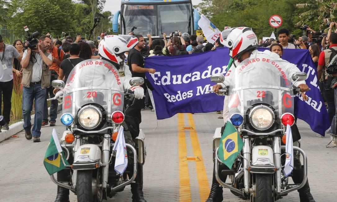 Batedores observam manifestantes cercarem o ônibus da seleção na chegada à Granja Comary Foto: Alexandre Cassiano