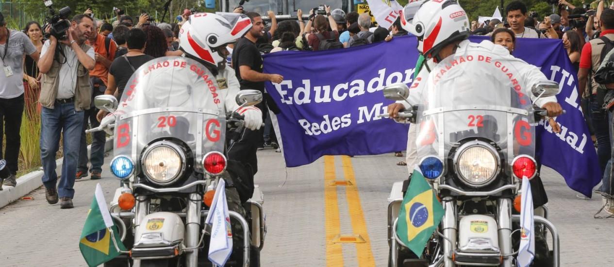 Batedores observam manifestantes cercarem o ônibus da seleção na chegada à Granja Comary Foto: Alexandre Cassiano / Alexandre Cassiano