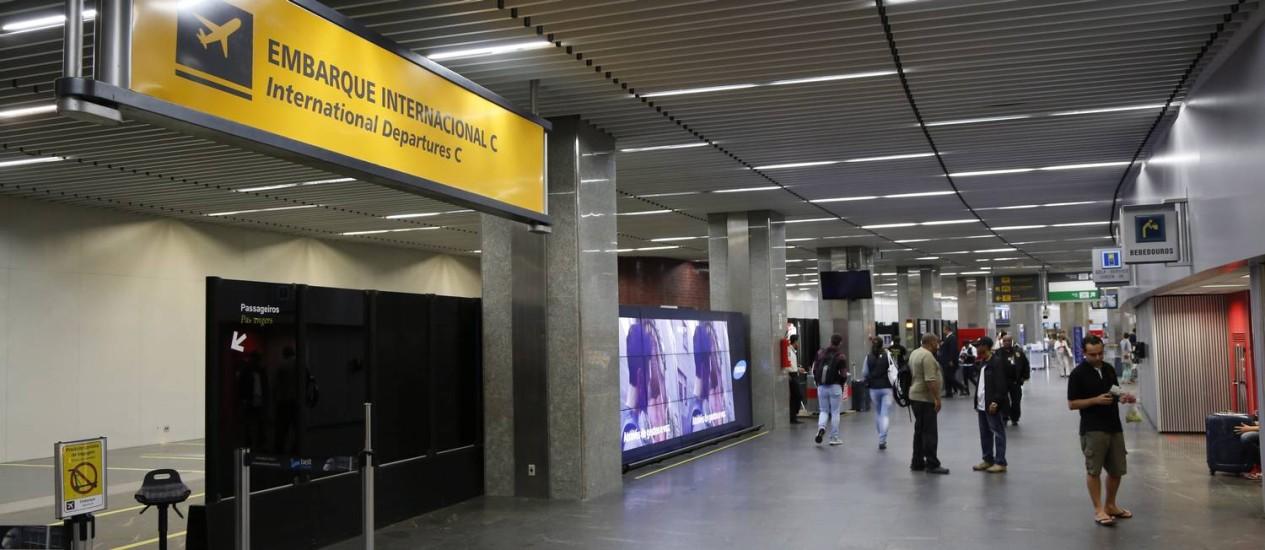 O embarque internacional no Terminal 1 é indicado com uma placa amarela e letras cinza. Uma das missões da nova concessionária é revitalizar a sinalização do aeroporto, padronizando a comunicação visual Foto: Fabio Rossi / Agência O Globo