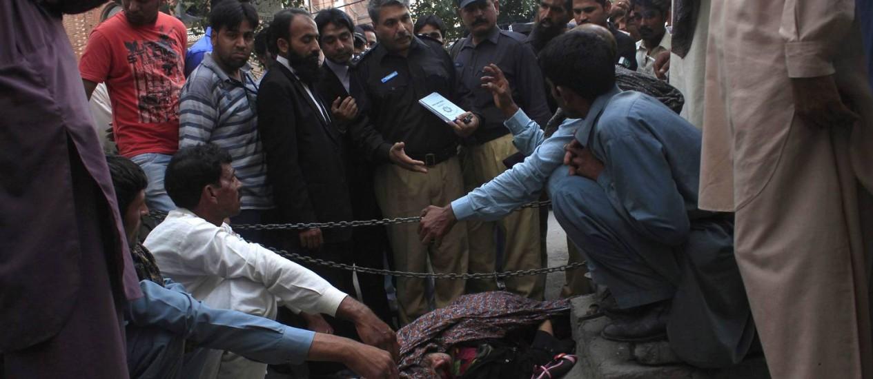 O corpo de Farzana Iqbal, apedrejada pela família, diante do tribunal em Lahore Foto: REUTERS