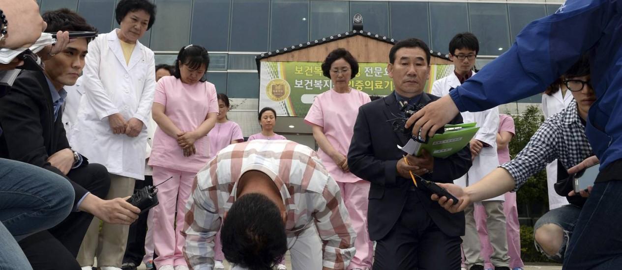 Funcionários de hospital se ajoelham para pedir perdão a vítimas de incêndio em hospital na cidade de Jangseong, na Coreia do Sul Foto: Hyung Min-woo / AP