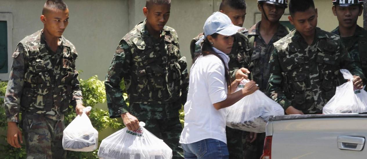 Mulher oferece bebidas a soldados tailandeses fora do Clube do Exército em Bangcoc Foto: CHAIWAT SUBPRASOM / REUTERS