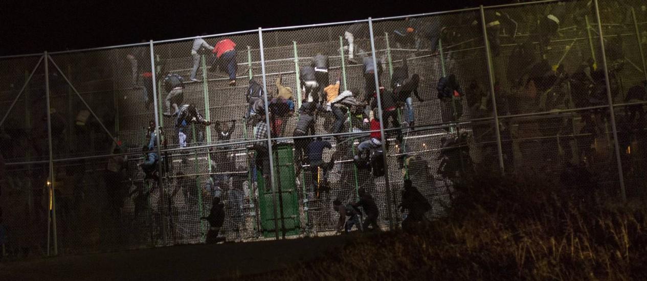 Imigrantes subsarianos escalam cerca metálica que divide Marrocos do enclave espanhol de Melilla Foto: Santi Palacios / AP