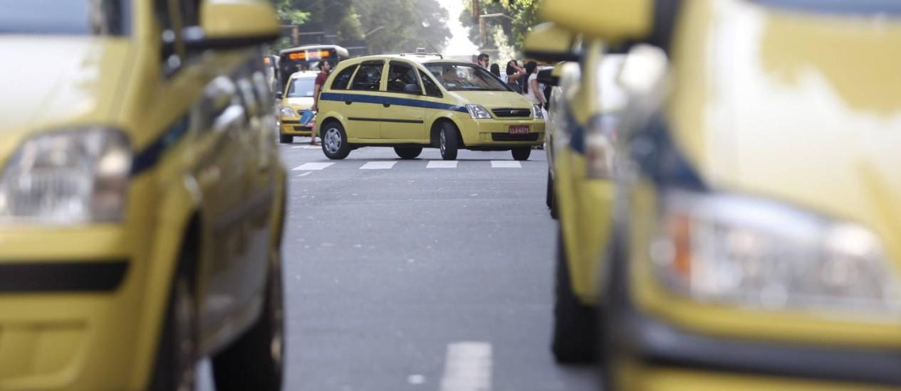 Táxis comuns, os amarelos com uma faixa azul escura na lateral e placa vermelha, devem obrigatoriamente ligar o taxímetro Foto: Gustavo Stephan / Agência O Globo